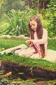 picture of fish pond  - Little girl feeds fishes in the pond - JPG