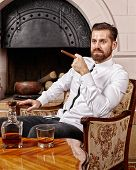 image of scotch  - Businessman relaxing with a glass of scotch and a cigar by the fireplace - JPG