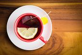 foto of brew  - Cup of freshly brewed healthy herbal tea with a lemon slice served in a red cup and white saucer on a wooden table with copyspace view from above - JPG