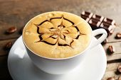 foto of latte  - Cup of coffee latte art with grains and chocolate on wooden table - JPG