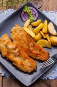 foto of cod  - Fried fillet of cod with french fries on a dark plate - JPG