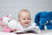 stock photo of girl toy  - Happy baby girl reading a book with little toy friends - JPG