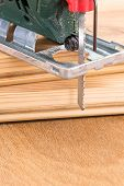 image of fret  - Wood planks cutting with electric fret saw tool - JPG