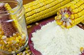 image of corn  - A jar with corn flour and corn ear on a wooden table - JPG