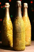 picture of champagne color  - Decorative champagne bottles on dark colorful spotted background - JPG