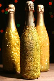 image of champagne color  - Decorative champagne bottles on dark colorful spotted background - JPG
