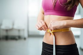 picture of measurement  - Slim young woman measuring her thin waist with a tape measure close up