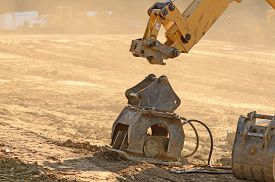 image of backhoe  - Backhoe hooking up to a powered compactor at a new commercial housing develpment - JPG