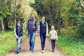 adventure, travel, tourism, hike and people concept - happy family walking with backpacks in woods poster