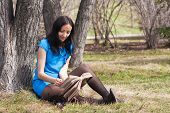 Girl Reading Book In Spring Park
