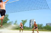Three Men Playing Beach Volleyball - Tall Clumsy Guy Spikes, Two Others Defend