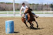 stock photo of barrel racing  - Man on horseback turning around a barrel and heading to the finish line during a barrel race - JPG