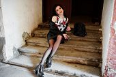 Young Goth Girl On Black Leather Skirt, Jacket And Punk Shoes Sitting On Stairs Of Old House And Lis poster