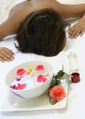 A woman awaits a sensual full body massage treatment showing a bowl of scented floral water and a bottle of massage oil
