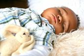 Beautiful toddler of mix parentage sleeping peacefully on sheepskin rug accompanied by his fluffy bunny toy.