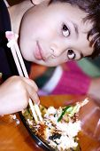 Young boy enjoying some Japanese prawn tempura and fried sushi, trying them with a pair of chopstick