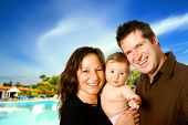Young family enjoying a sunny holiday with a young baby.