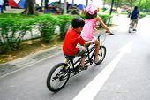 Dos niños pequeños, montado en una bicicleta tándem en un parque público