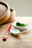 picture of chinese food  - Two local calamansi limes in traditional Chinese setting with chopsticks and white china spoon on bamboo matting - JPG