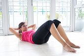 Young fitness woman doing her crunching exercise for leaner stomach muscle
