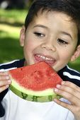 Young boy enjoying a red juicy watermelon
