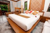 Beautiful kingsize bed in a tropical hotel bedroom.