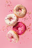 Various decorated doughnuts in motion falling on pink background. Sweet and colourful doughnuts fall poster