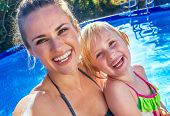 Happy Active Mother And Child In Swimming Pool Taking Selfie poster