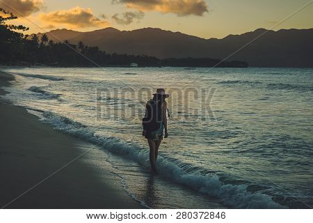 poster of Traveler Girl Walking On Tropical Beach In Sunset.vintage Photo Of Young Girl Traveler In Vacation.