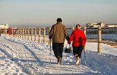 HASTINGS, ENGLAND - DECEMBER 3: A mature couple walk on the snow covered seafront on December 3, 2010 at Hastings, East Sussex. It is the coldest Winter in Britain for 100 years.