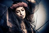 stock photo of wicca  - woman in dancing motion  under black veil with wreath of flowers in hair - JPG