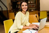 Image of a young student happy woman in library doing homework studying read and using laptop comput poster