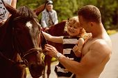 Equine Therapy, Recreation Concept. Girl With Man Pet Horse On Sunny Day. Child With Muscular Macho  poster
