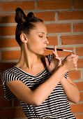 woman with cigarette on brick wall background