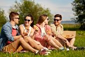 friendship, leisure and food concept - group of smiling friends eating pizza at picnic in summer par poster