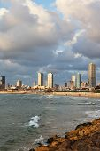 The fluffy clouds shined with the sunset sun, over magnificent hotels of quay in Tel -Aviv. poster