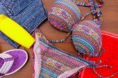 Set Of Beachwear On Wooden Background. Sunscreen, Towel, Swimsuit, Jean  Shorts And Flip-flops. Summ poster
