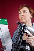 Woman On Ladder Holding Nail Gun