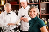 Restaurant manager smiling with staff at wine bar