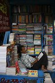 KOLKATA (CALCUTTA) - DECEMBER 15: An unidentified seller reads book in small street book shop on Dec
