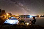 Night Camping On Lake Shore. Man And Woman Having A Rest Near Tent, Couple Sitting On Chairs Near Bo poster