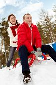 Portrait of happy couple tobogganing during winter vacation