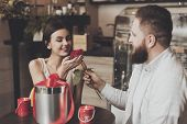 Bearded Man Gives A Rose To Beautiful Smiling Girl. A Young Man With A Beautiful Young Girl Sitting  poster