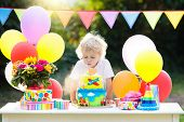 Kids Birthday Party. Child Blowing Out Candles On Colorful Cake. Decorated Garden With Rainbow Flag  poster