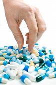 stock photo of take responsibility  - hand taking pills from the heap of different medications