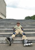 The boy with roller blades rests on the sta
