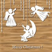 stock photo of little angel  - Christmas background with angels cut of paper on wood - JPG