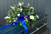 stock photo of crematory  - A blue coffin in a morgue with a flower arrangement - JPG