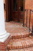 stock photo of entryway  - Pretty brick steps leading up into an entryway with old wood doors - JPG