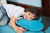 Cute little boy lying on heartshaped pillow in kindergarten